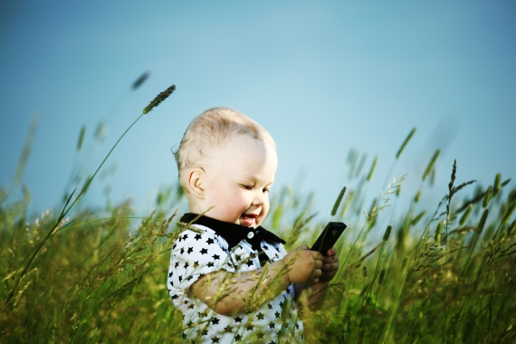 boy in grass call by phone